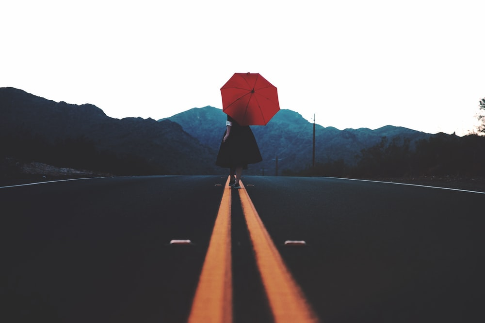 woman walking in the middle of the road with umbrella during day