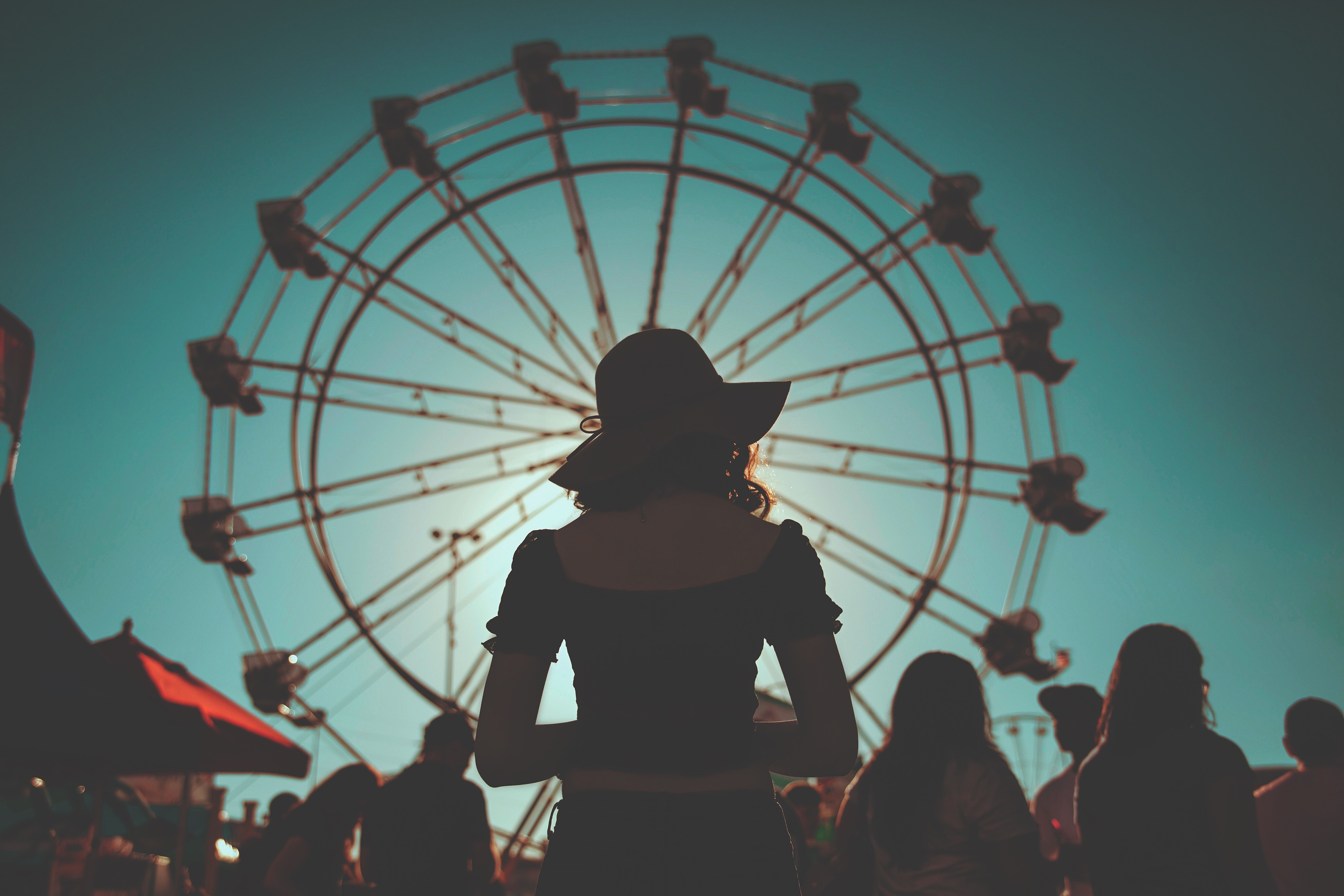 woman standing in front of ferris wheels surrounded with people