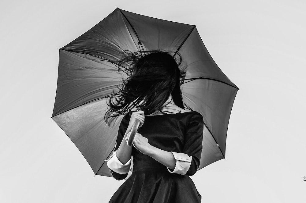 grayscale photo of woman holding umbrella