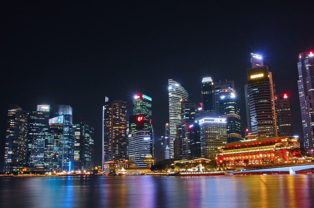 city buildings near bodies of water at night time