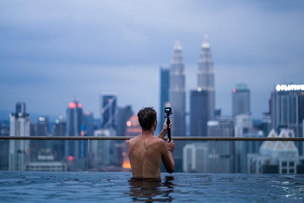 man using a camera to on a terrace pool view point