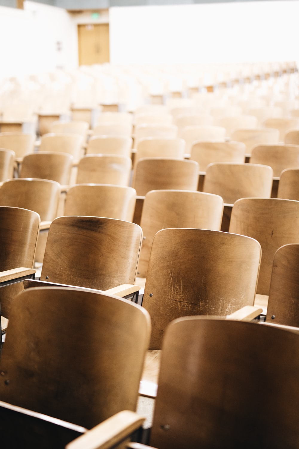 vacant brown wooden chair at stadium