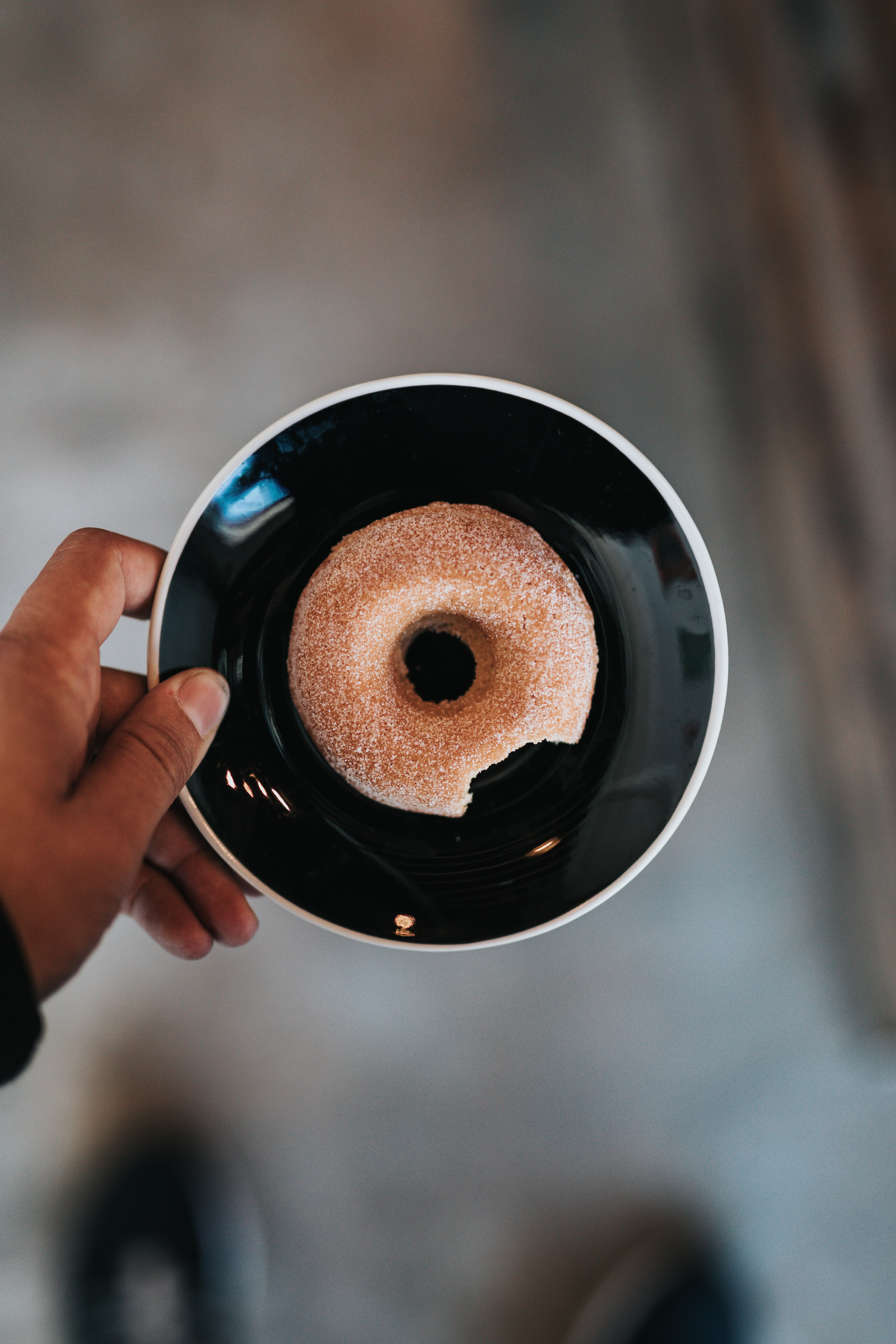 person holding black ceramic plate with donut