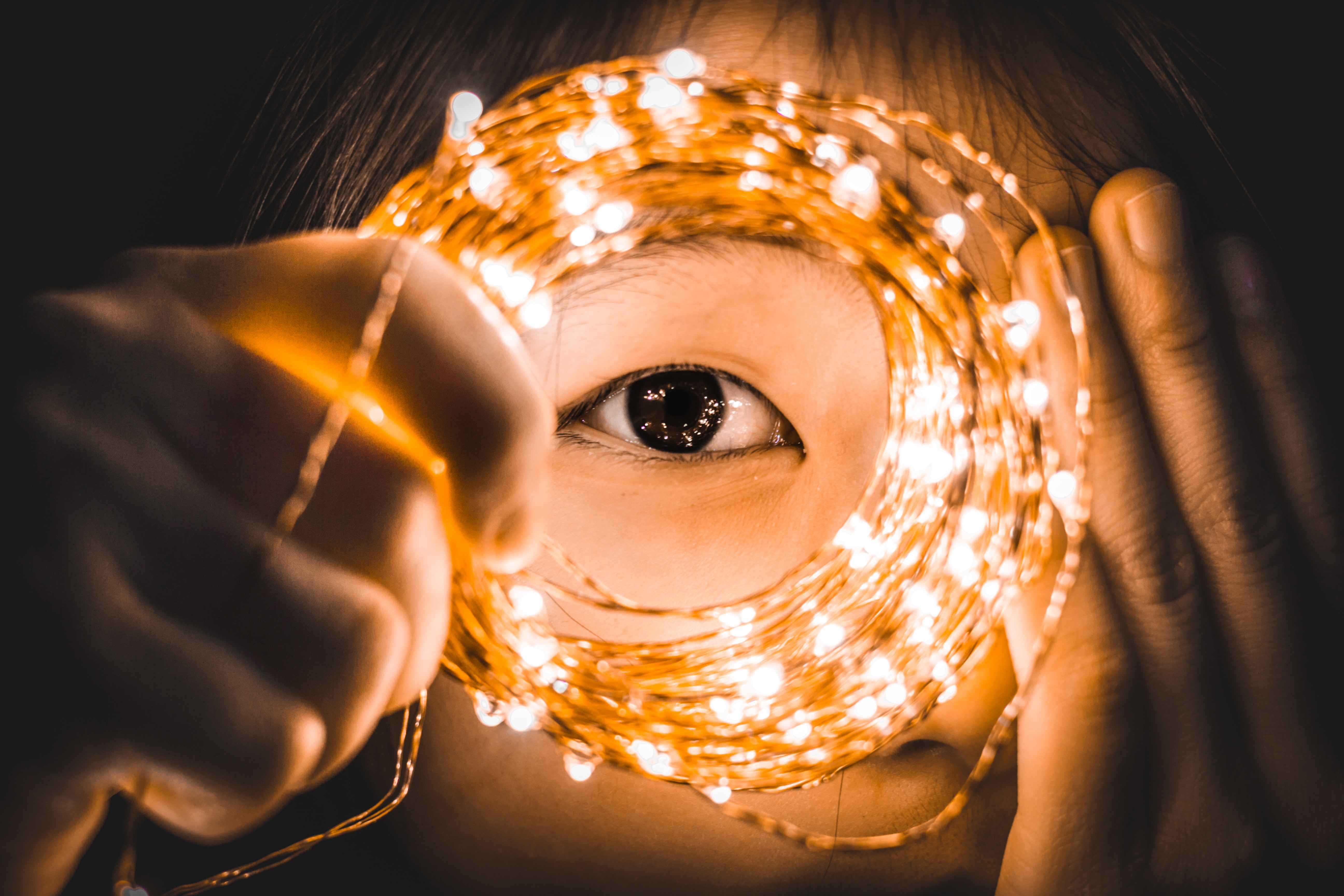 person covering one eye while holding yellow string lights