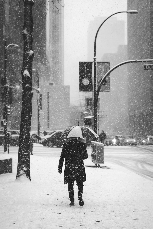 person holding umbrella standing near street light