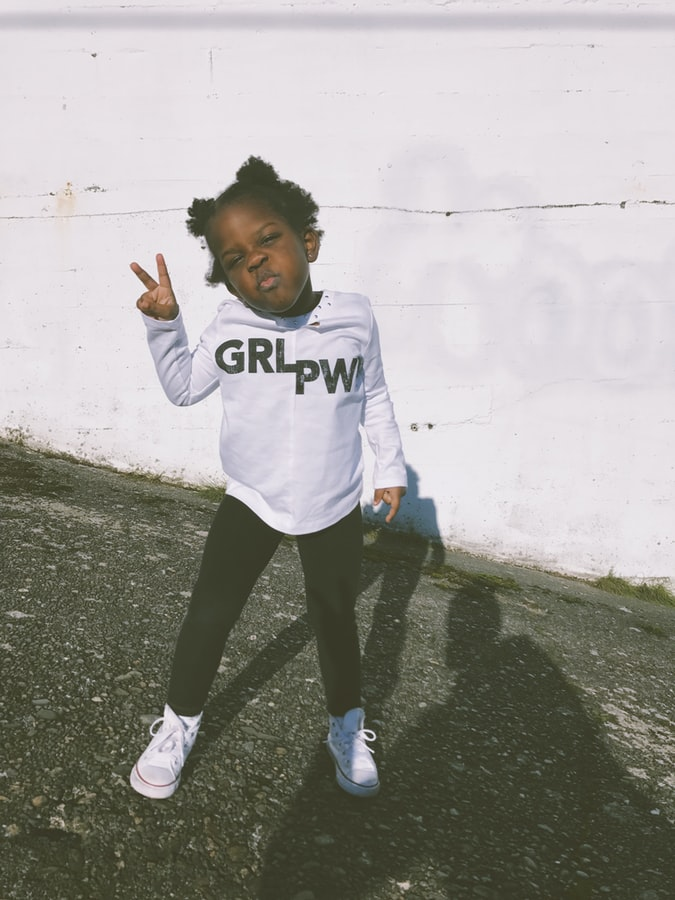 "A photo of a young black girl wearing a white t-shirt that says ""grl pwr"" on it, giving a peace sign and a fierce face to the camera."