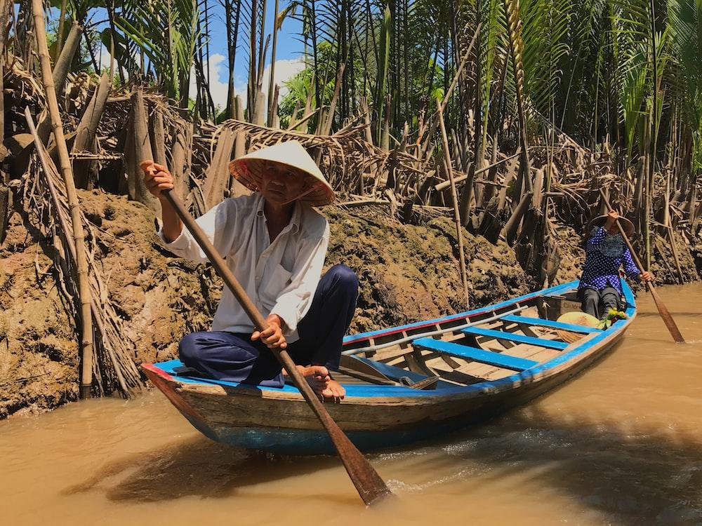 two men riding canoe on bridge