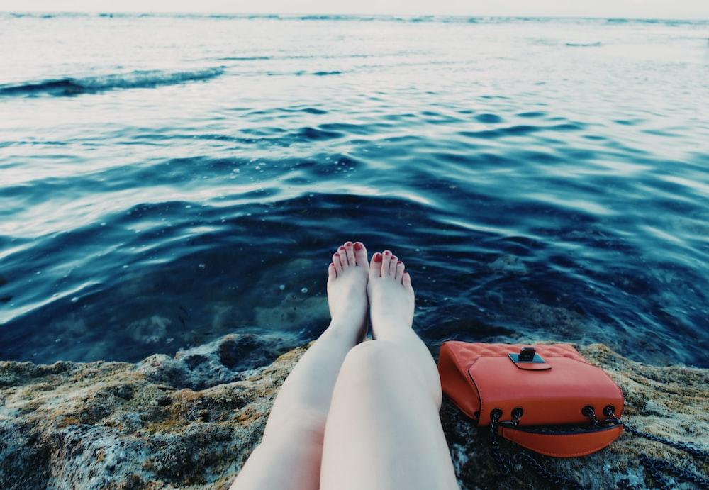 person sitting near rock beside body of water