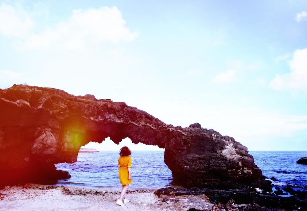 woman standing below arch on sea