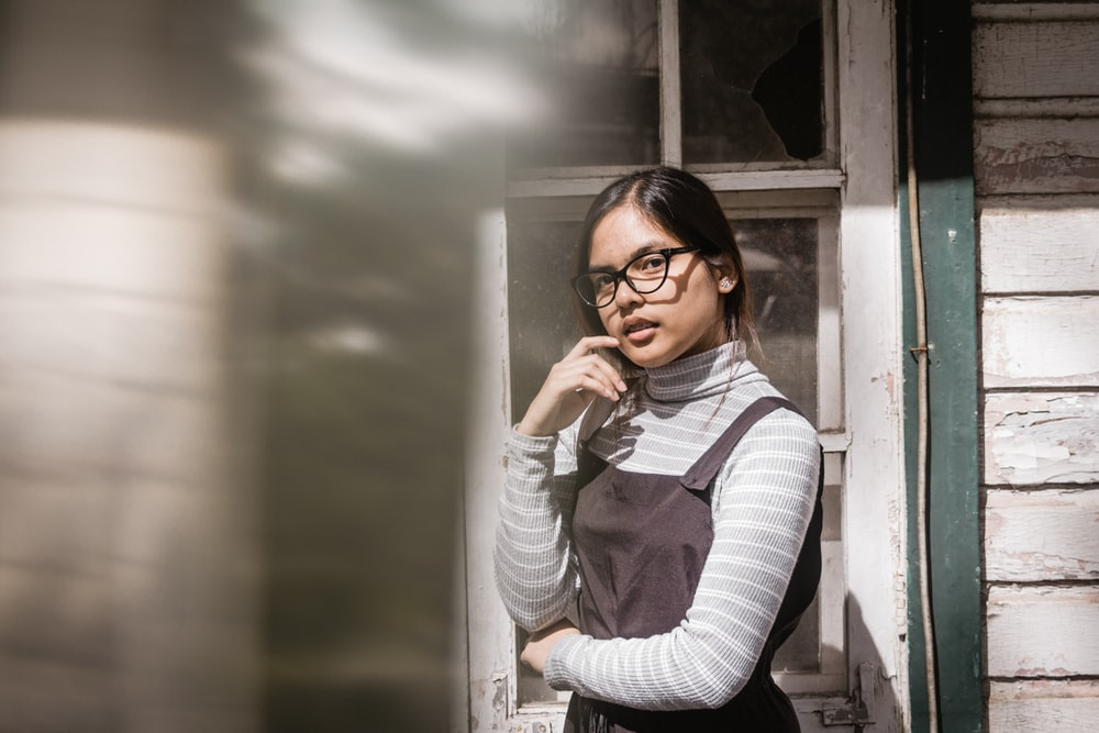 girl with gray and white striped turtle-neck long-sleeved shirt standing beside door panel