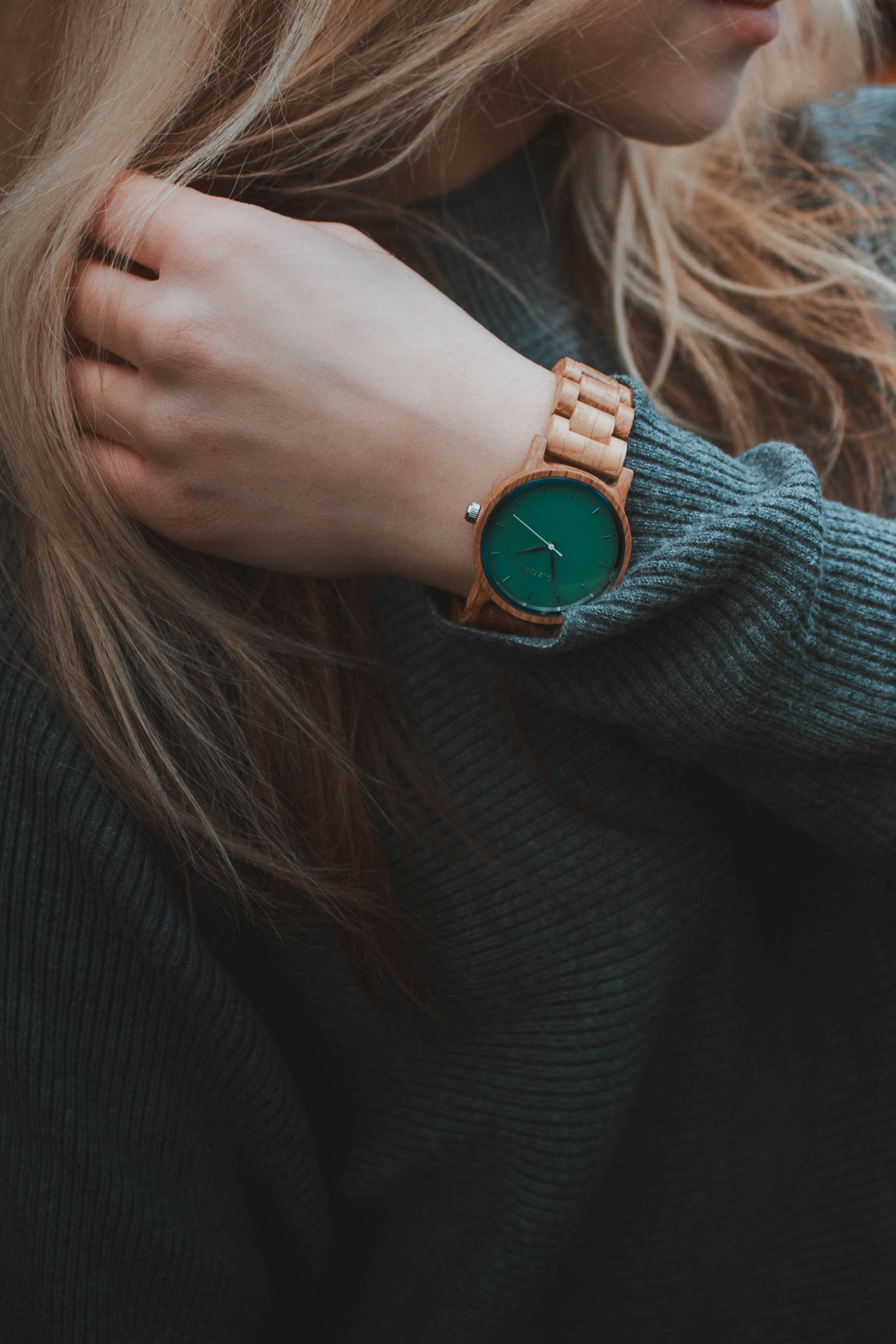 woman wearing gray sweater and gold-colored watch
