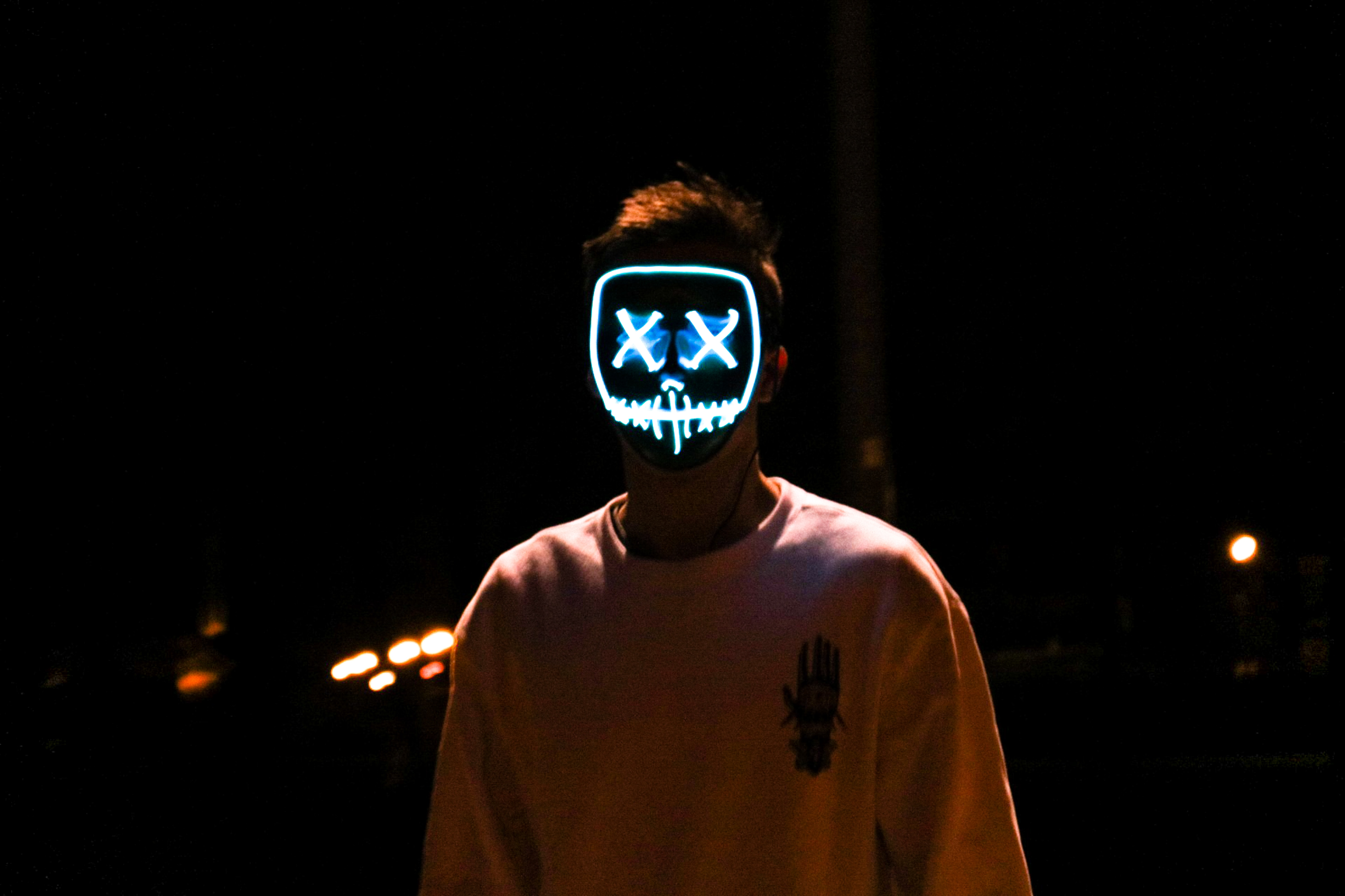man standing in the dark wearing lighted stitched mouth and crossed eyes mask