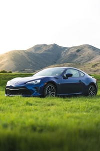 blue Toyota 86 coupe on green grass near mountain at daytime