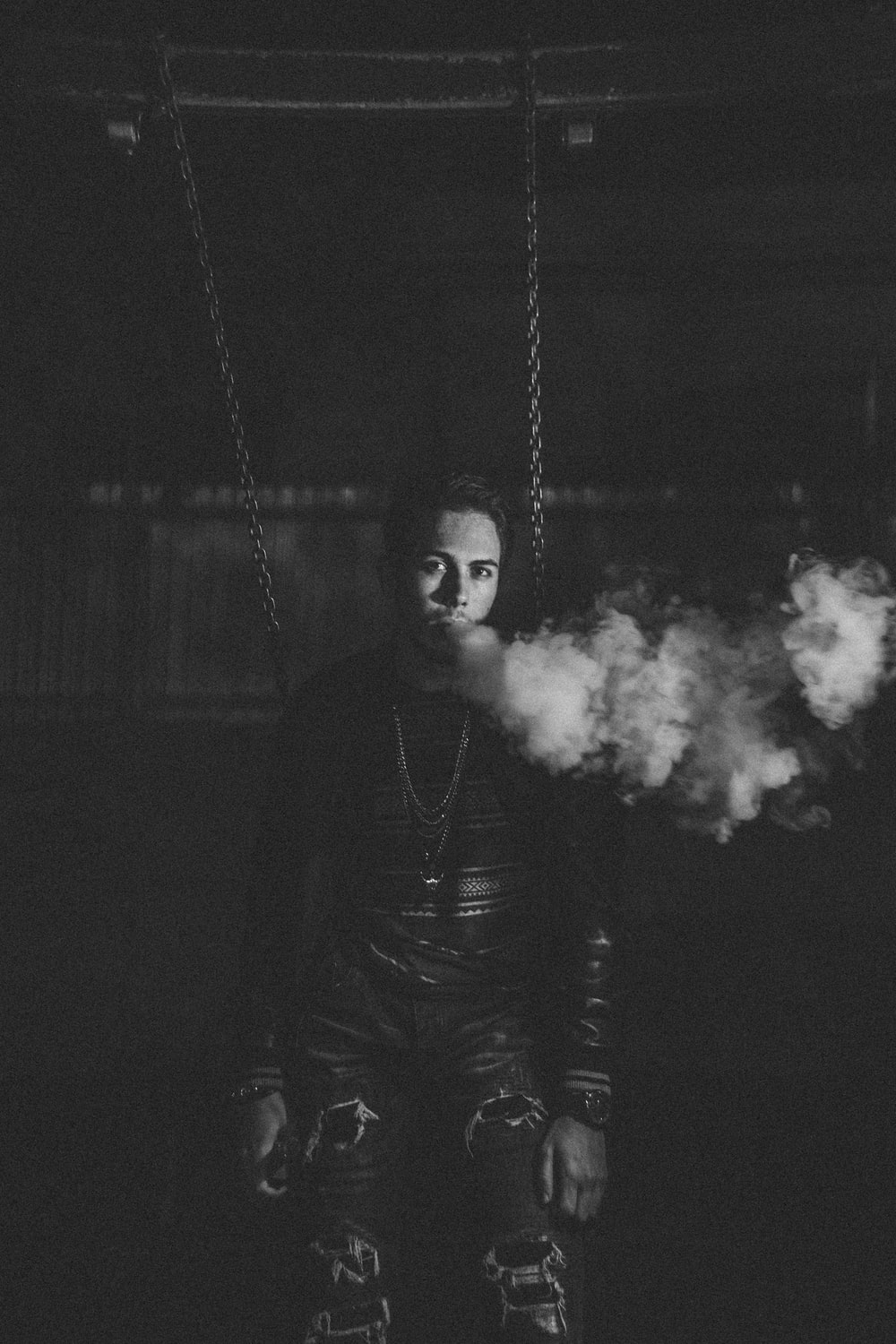 grayscale photography of man using vape