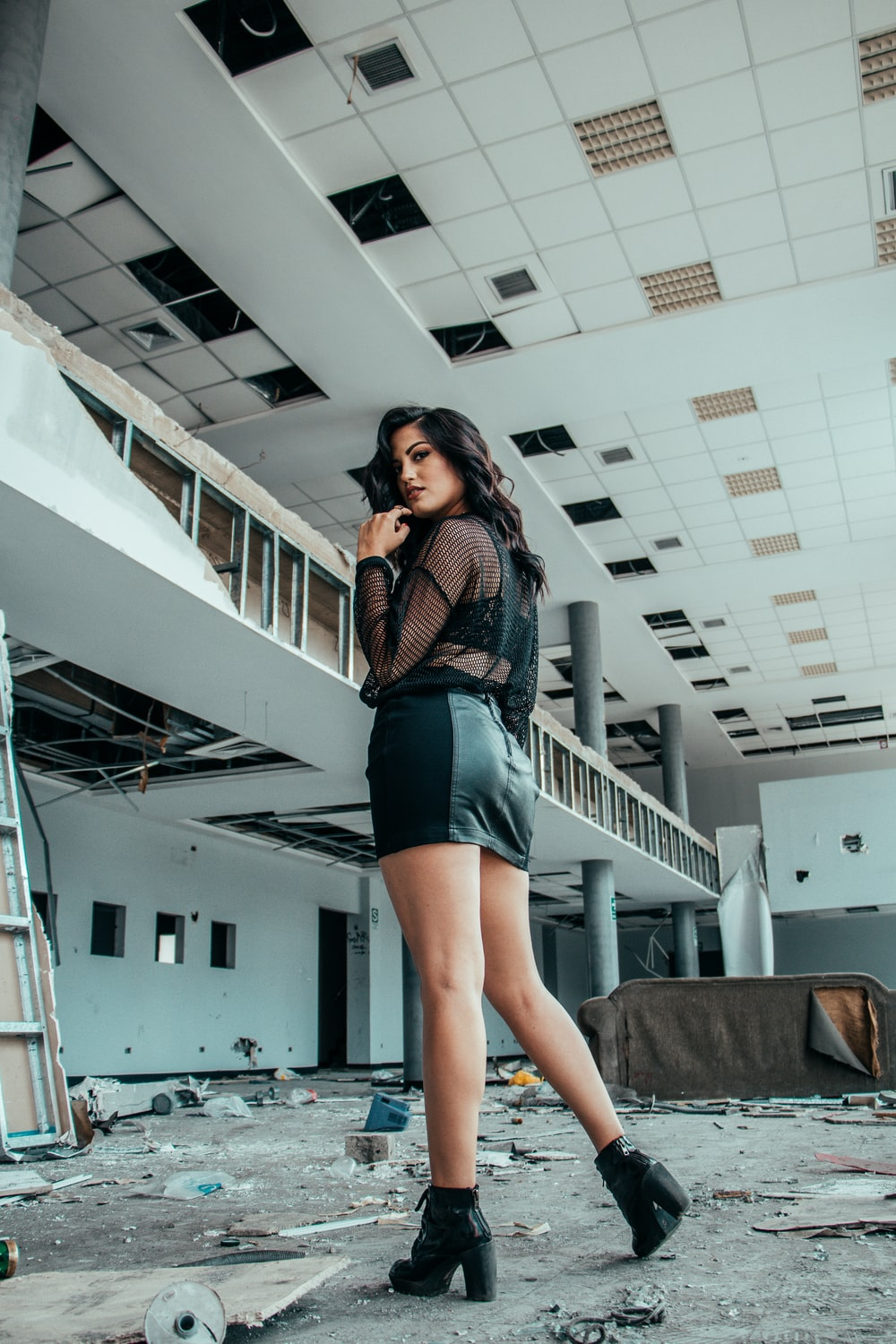 woman in black long-sleeved top and mini skirt standing on empty commercial building during daytime