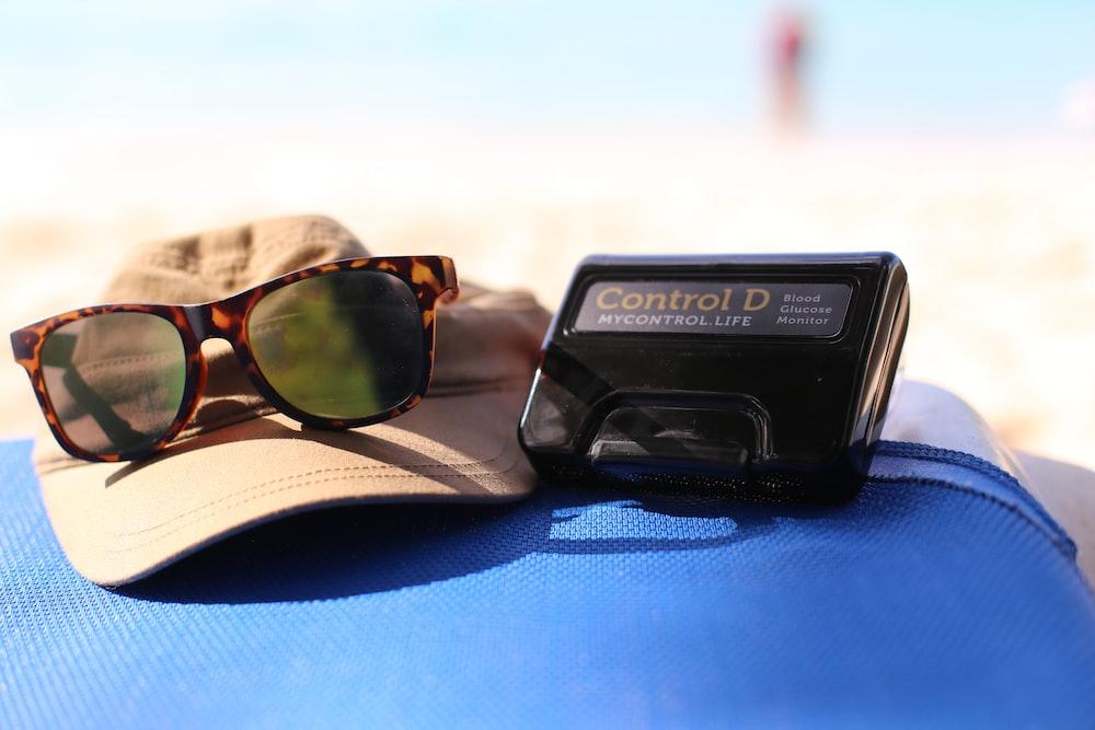 tortoiseshell framed sunglasses near black Control D device taken at daytime