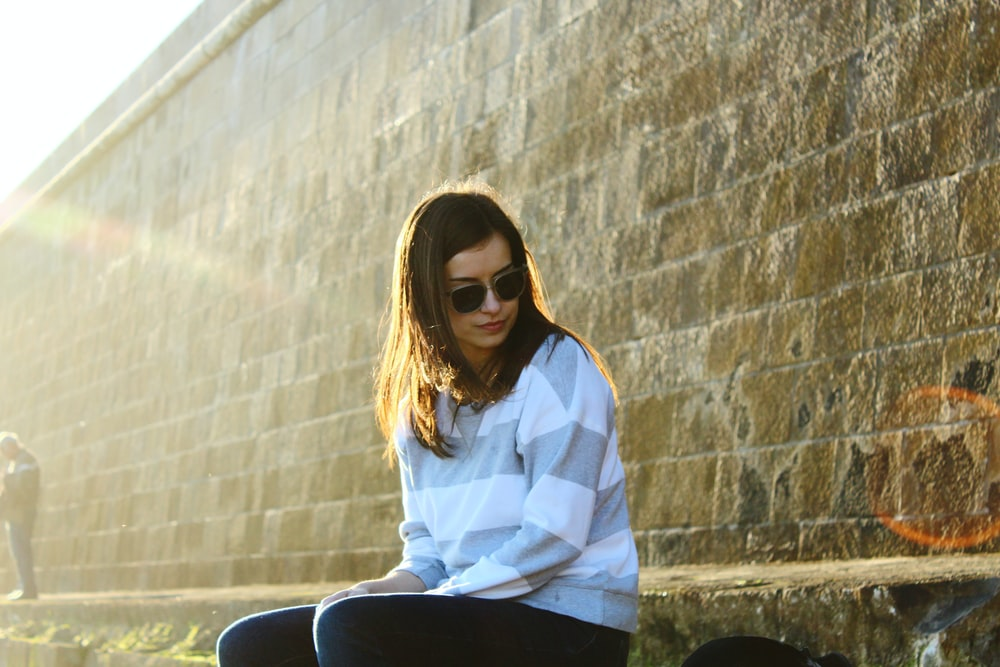 woman sitting beside brown concrete wall