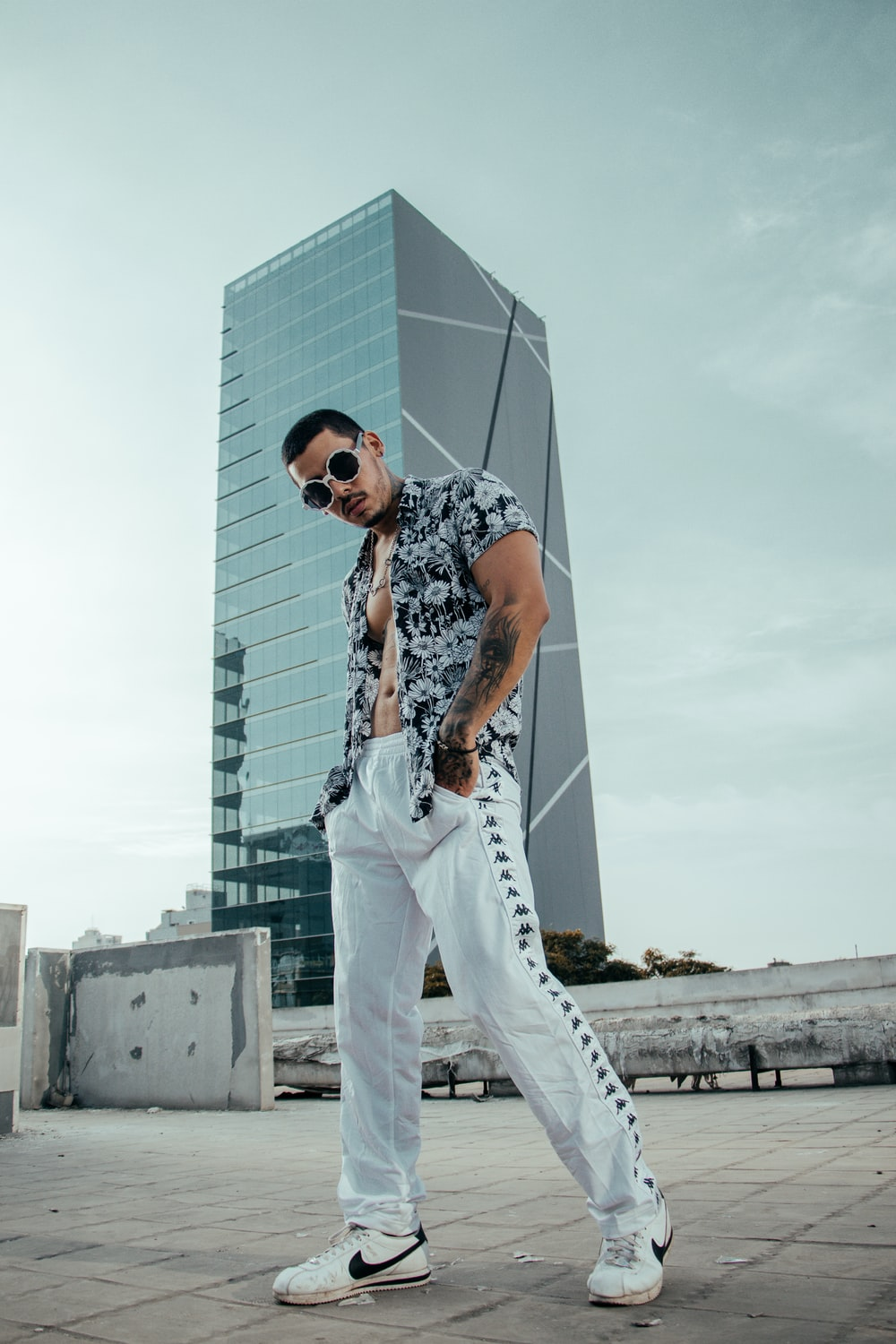 man in black and white floral button-up T-shirt wearing sunglasses near building during daytime