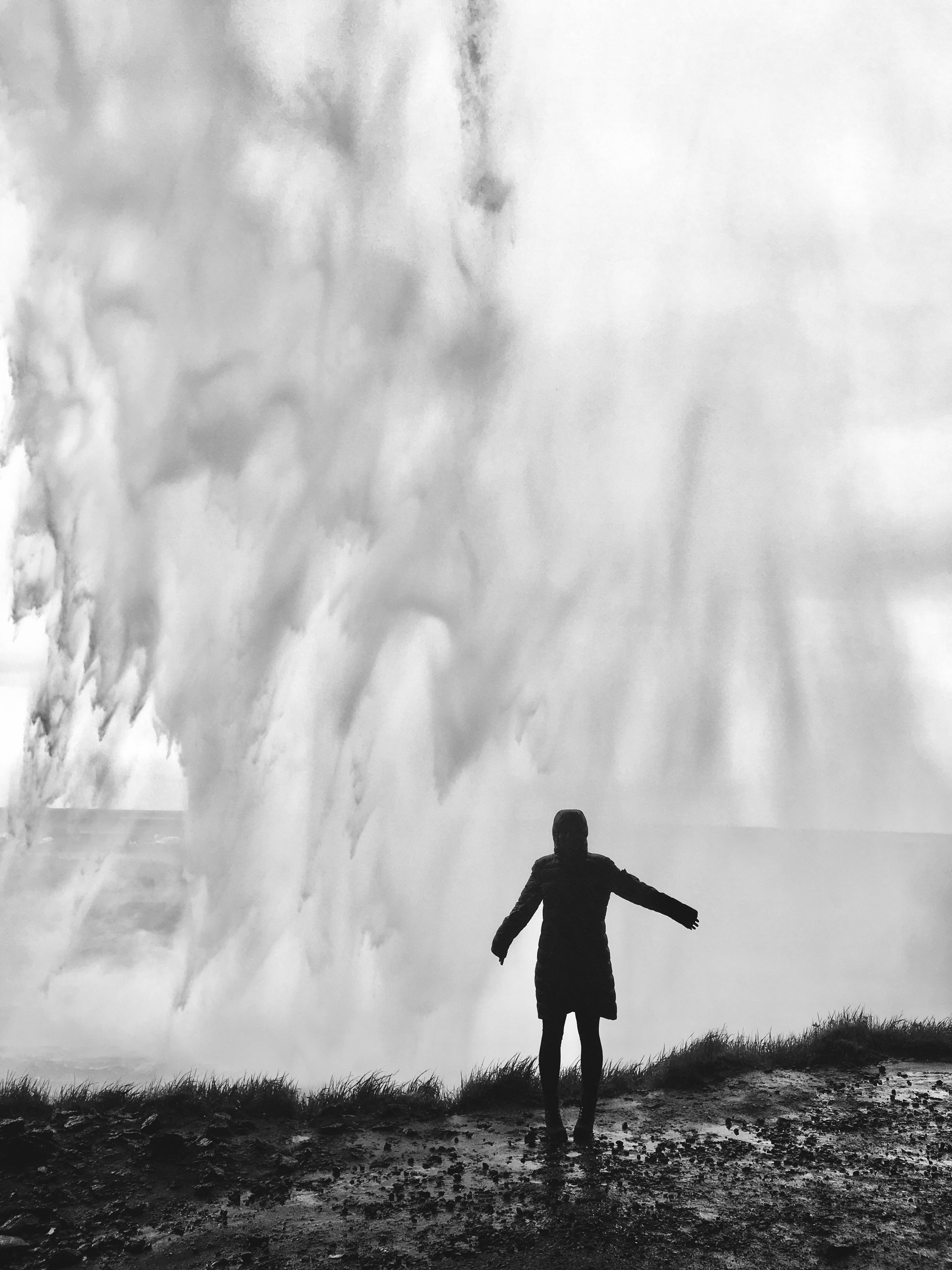 grayscale photography of person standing in front of splashing water waves