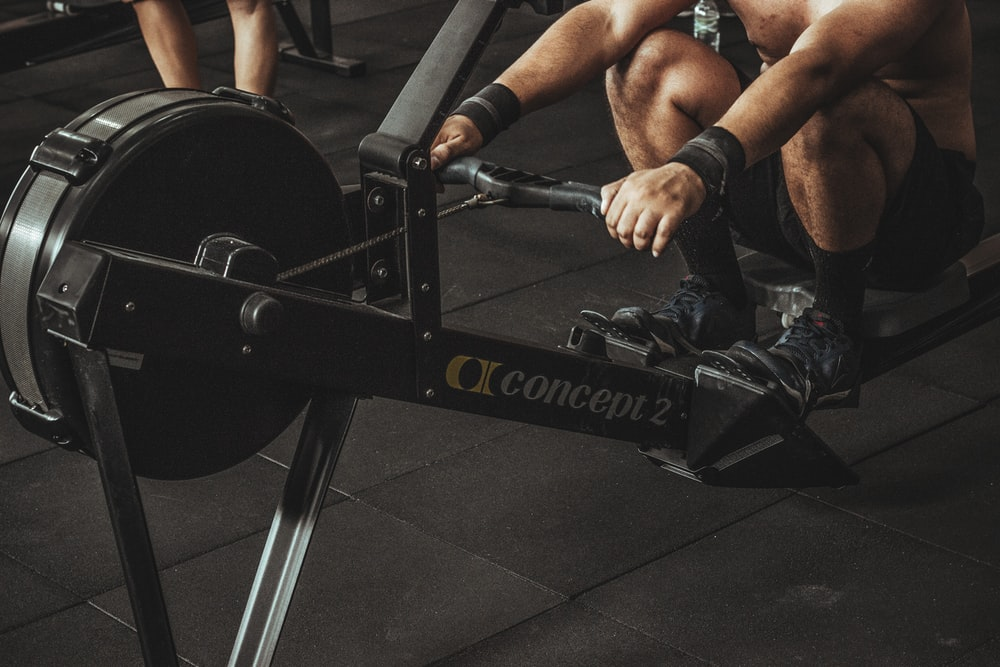 topless man using rowing machine