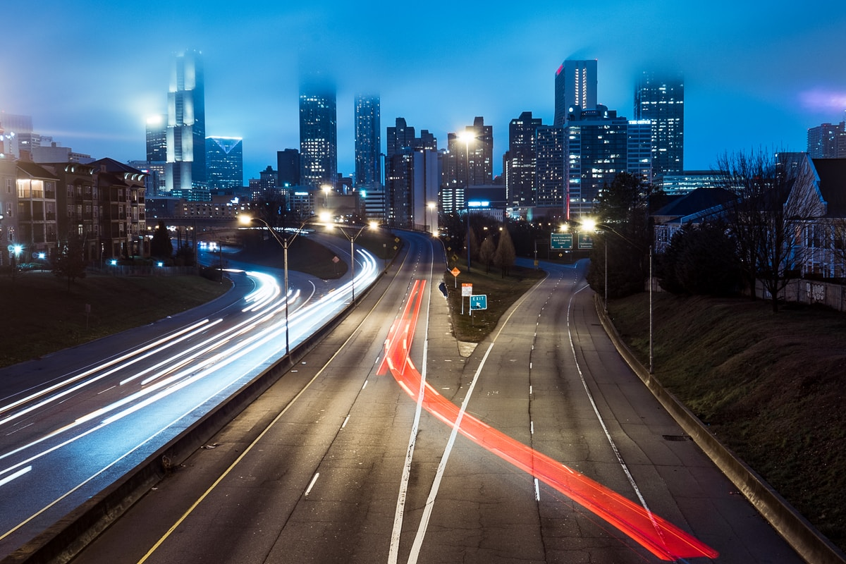 Am empty highway leading to a light downtown at night.  There are blue lights on the left and on the right is a divided lane with a red light cutting over avoiding the exit.