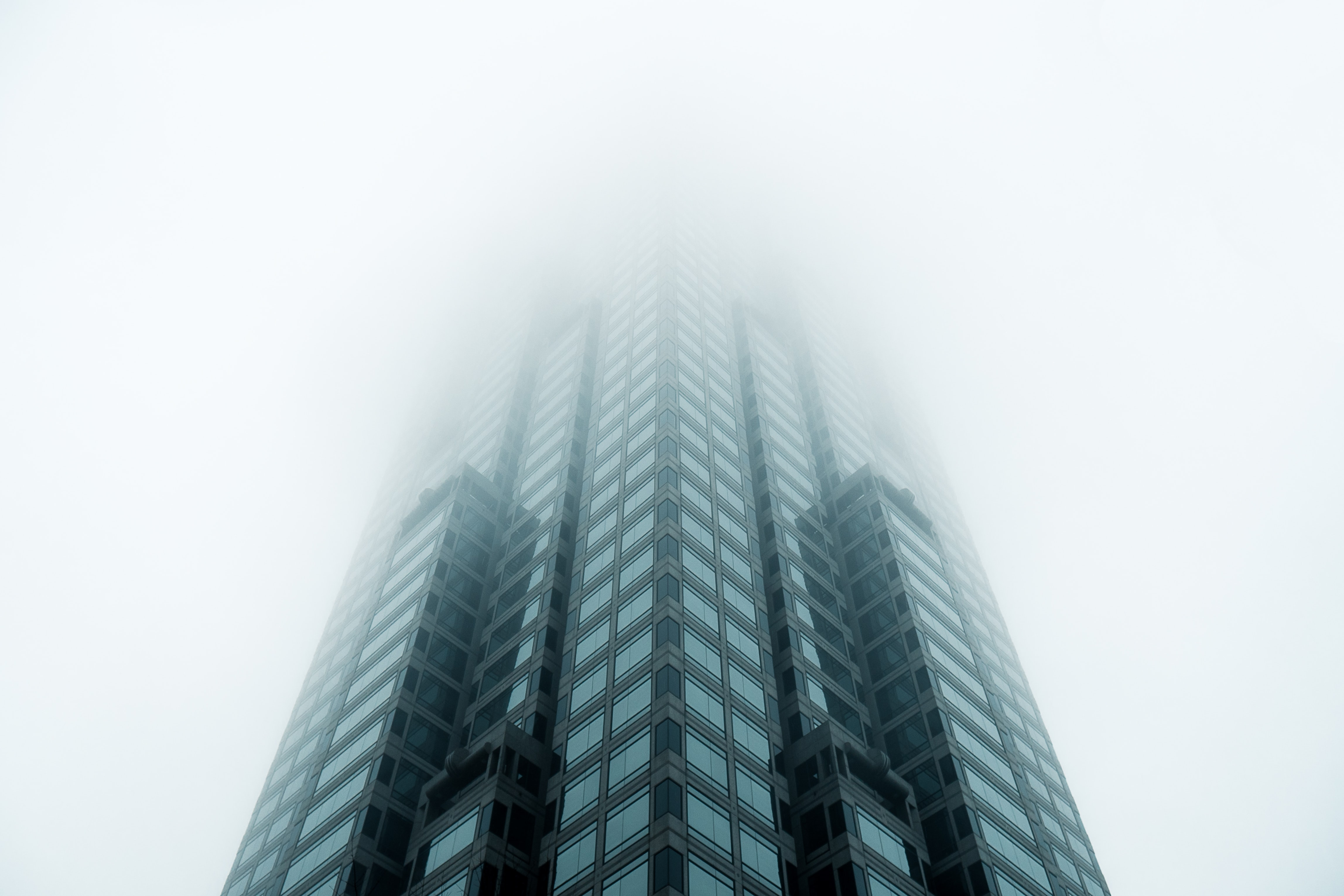 black high-rise building covered with fog