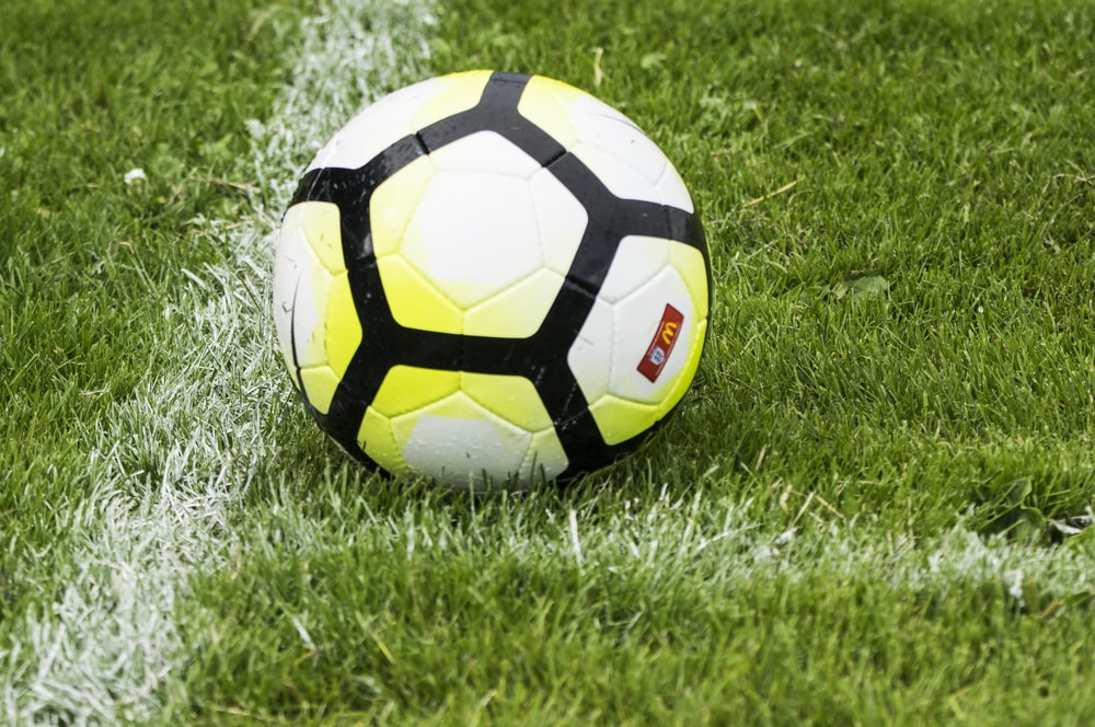 white and green soccer ball on green grass
