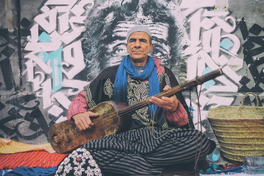 man playing string instrument beside brown basket