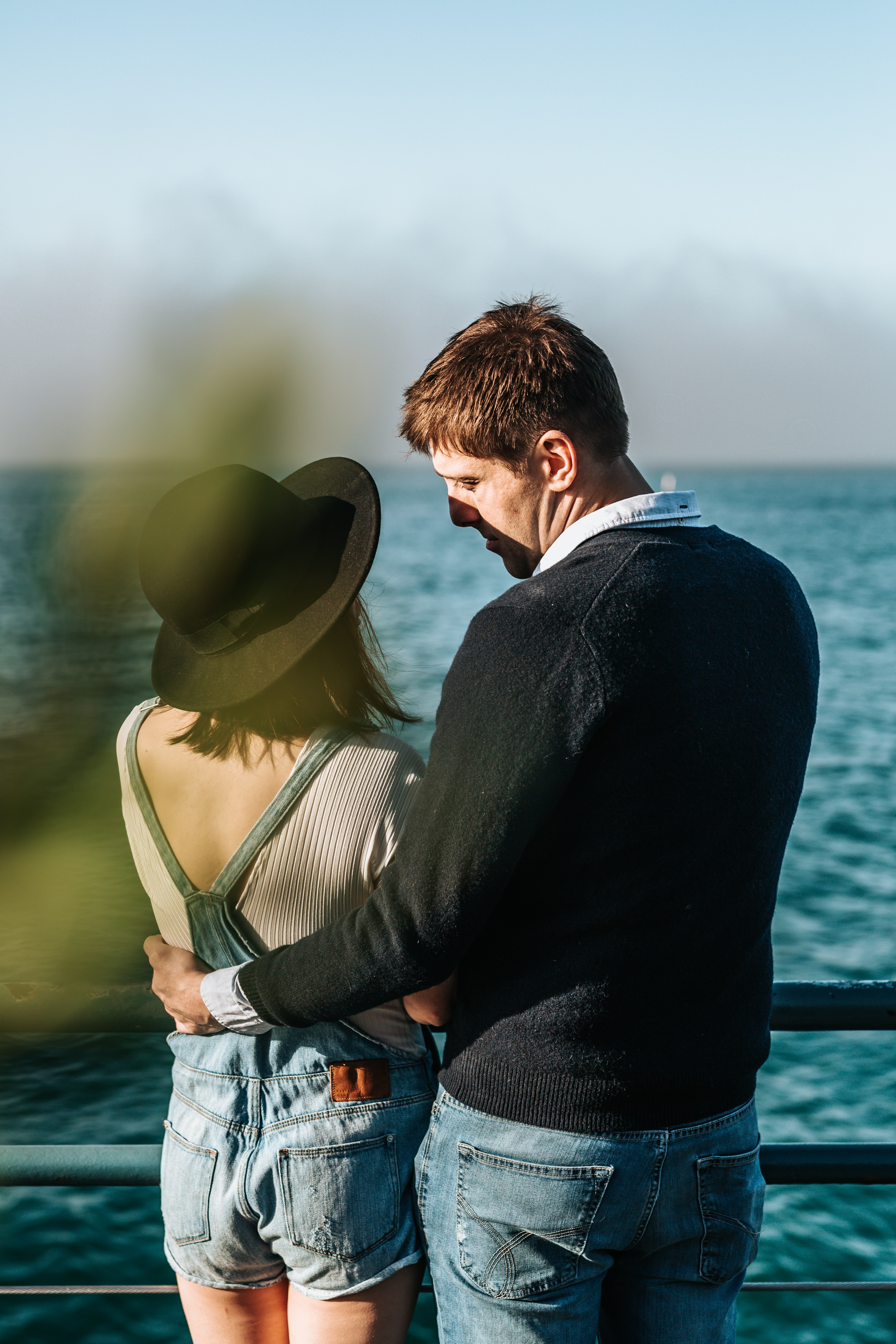 man and woman standing beside metal rail near body of water