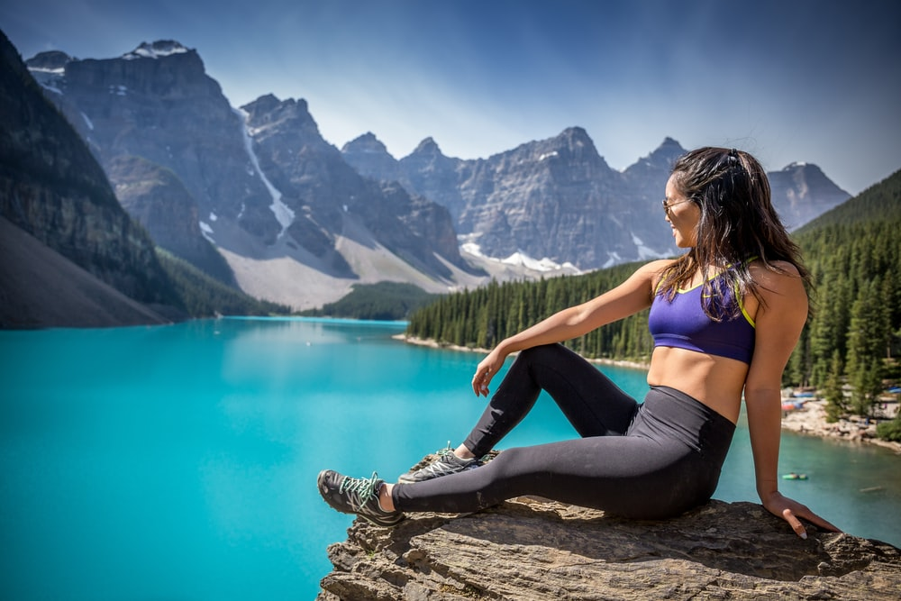 woman sitting on mountain cliff during daytime