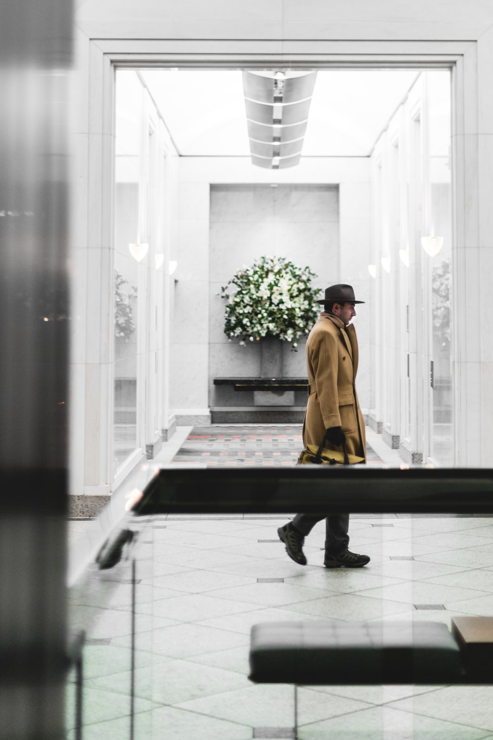 man holding brown bag while standing on hallway