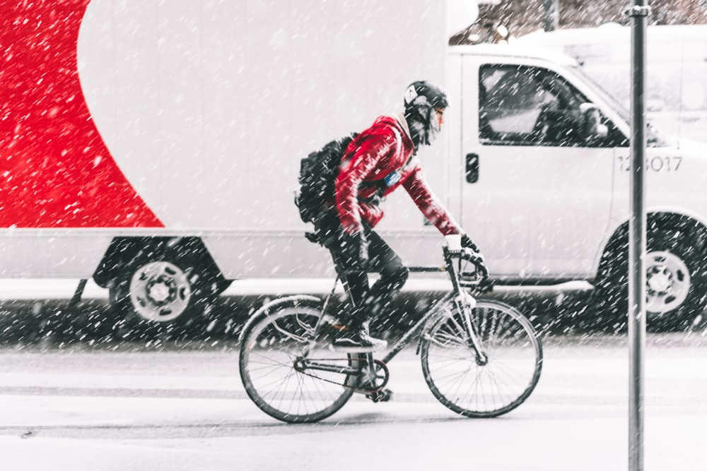 person in red jacket riding on mountain bike with white vehicle nearby during winter