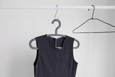 black sleeveless top hanging on wardrobe clothe teams background