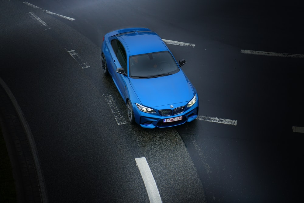aerial photography of blue sedan on highway