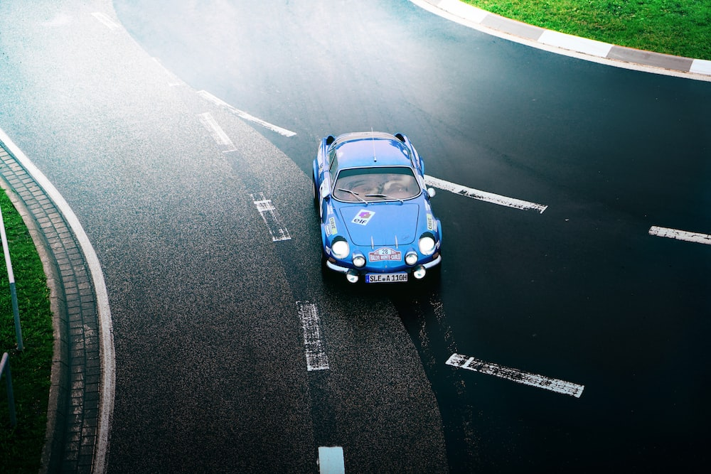 blue coupe on black road