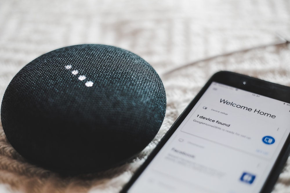 turned-on charcoal Google Home Mini and smartphone