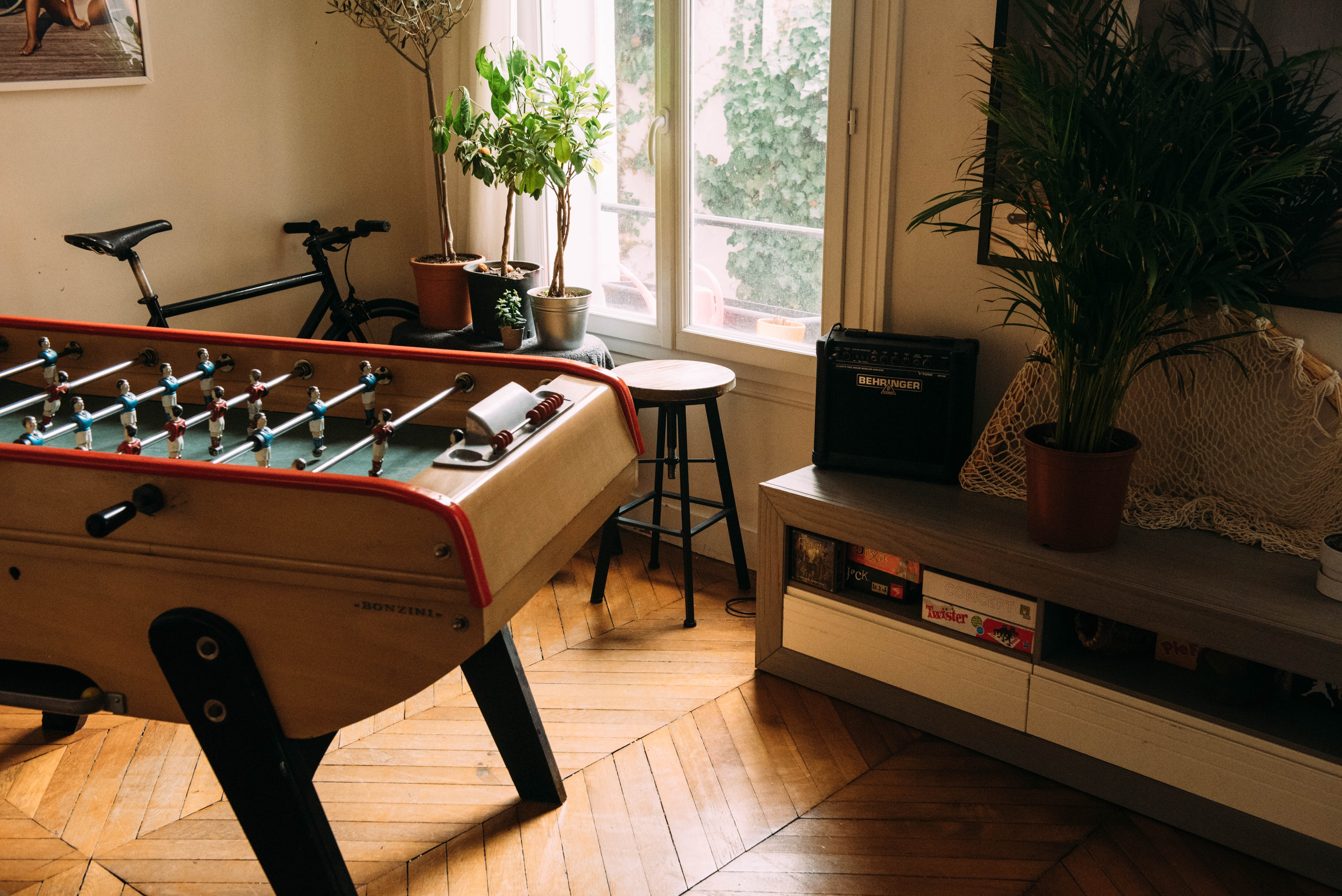 brown air hockey beside bicycle inside beige room