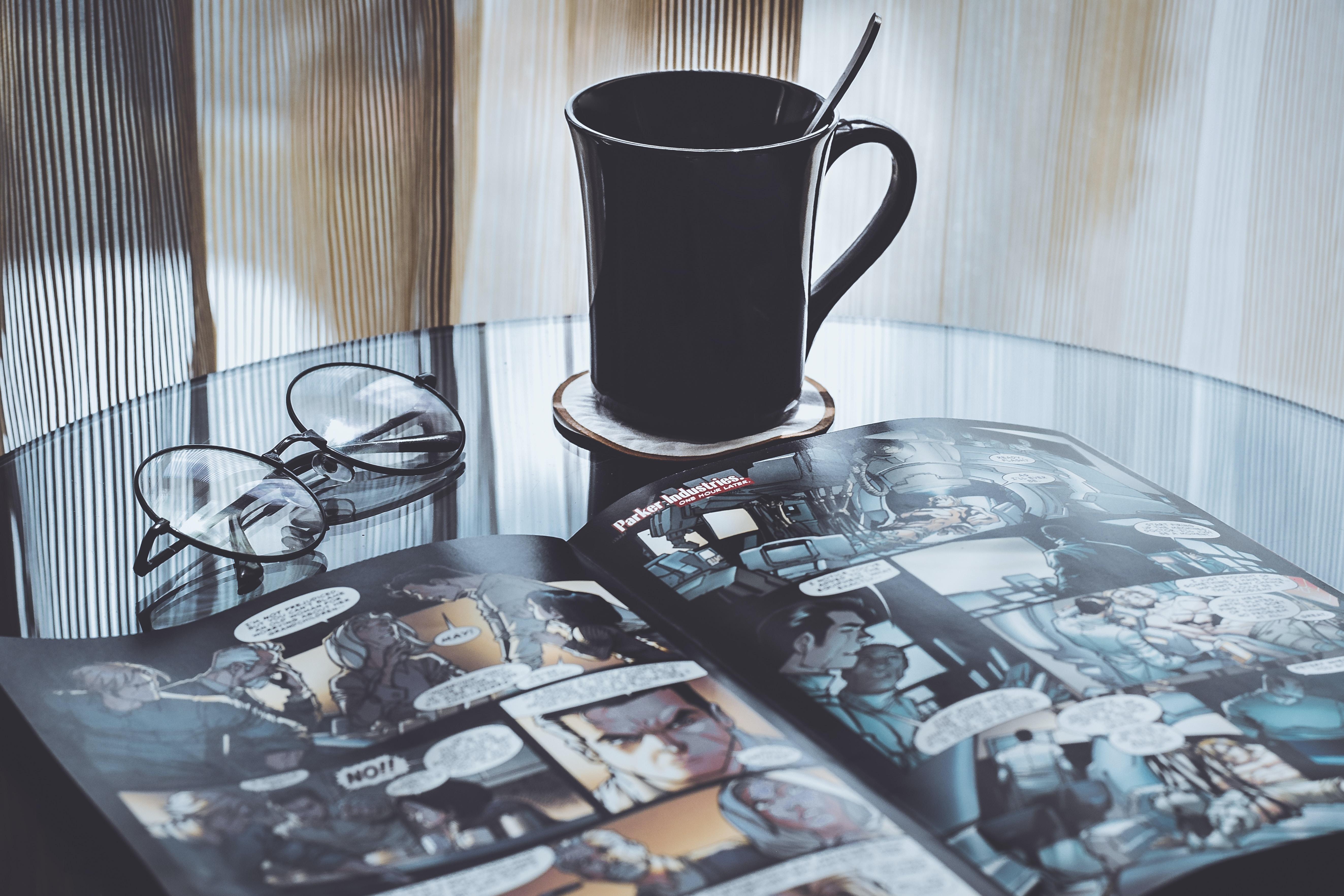 eyeglasses near mug on table