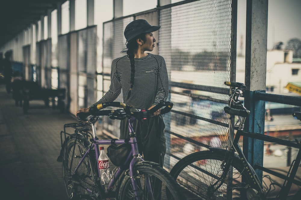 woman holding purple city bicycle