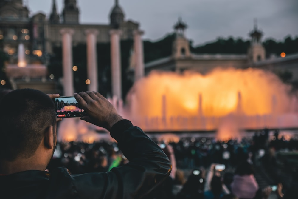 man capturing fountain at daytime