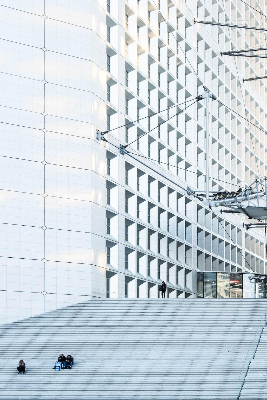 man standing beside white building