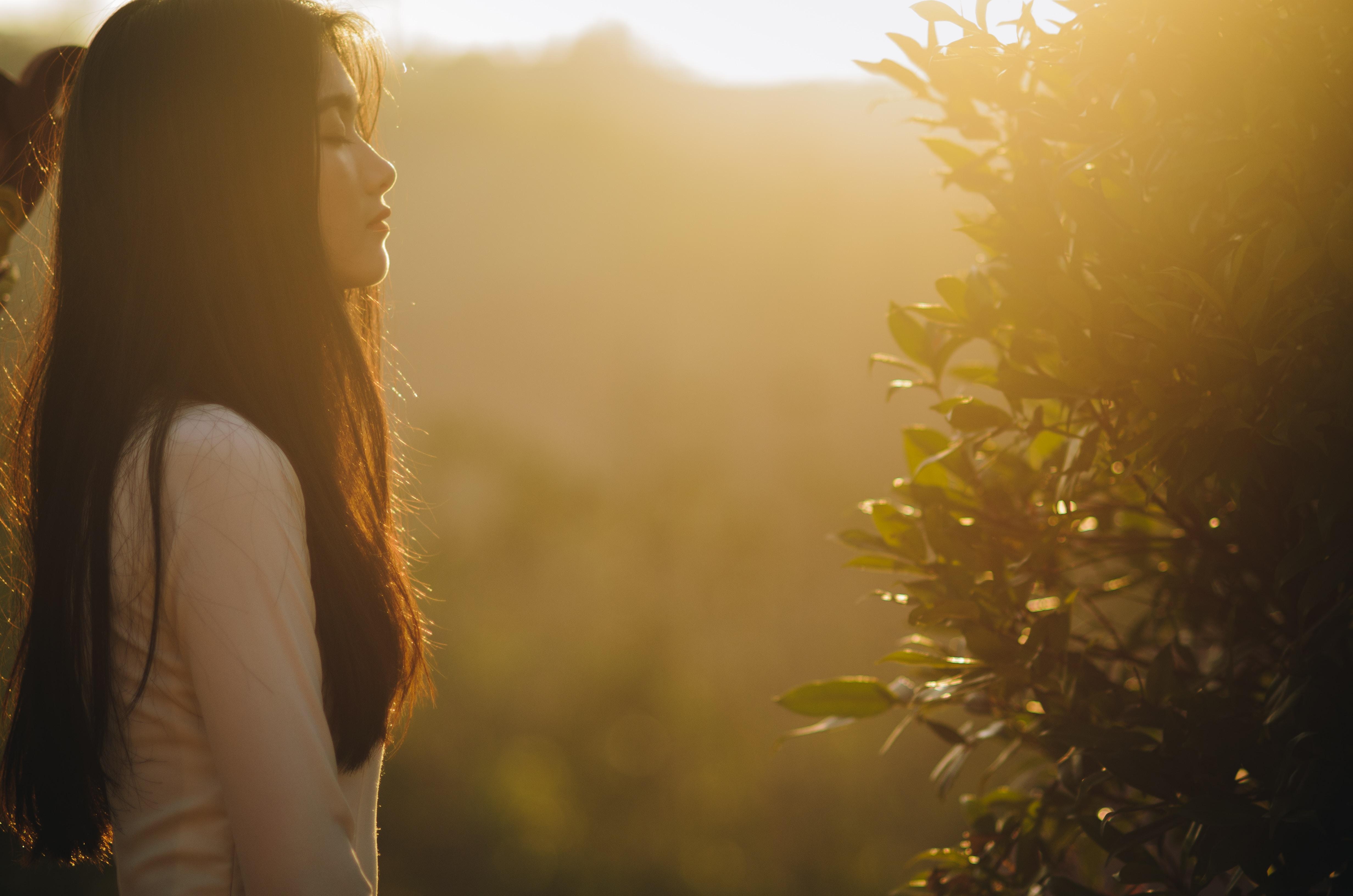 woman in brown shirt enjoying the sunrise