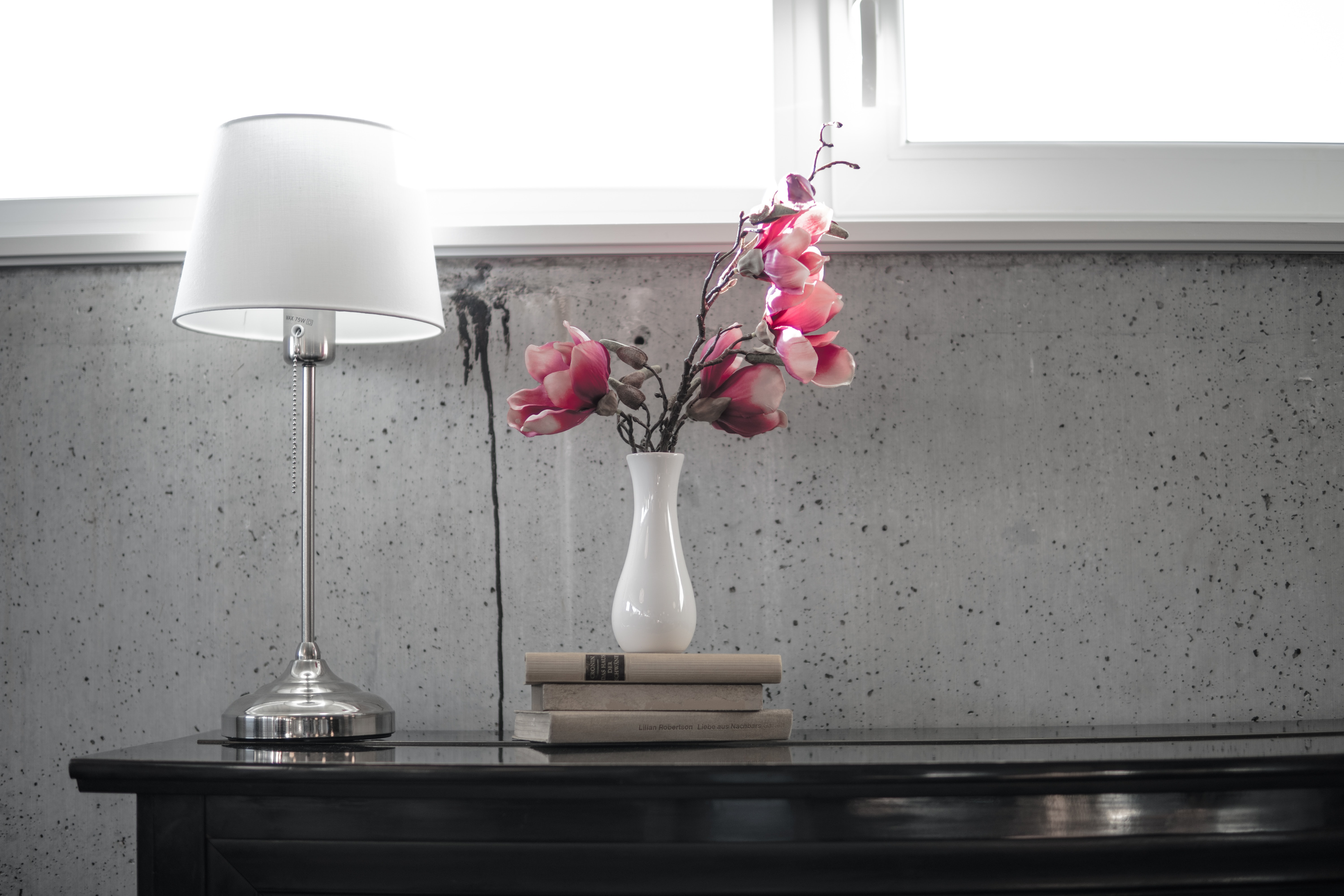 silver table lamp with white lampshade on top of black table