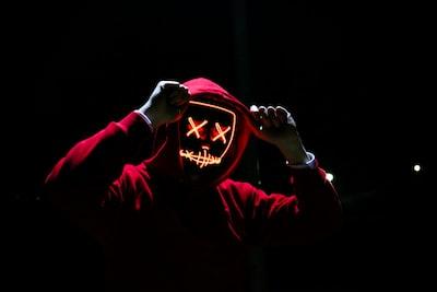 man wearing red hoodie skull teams background