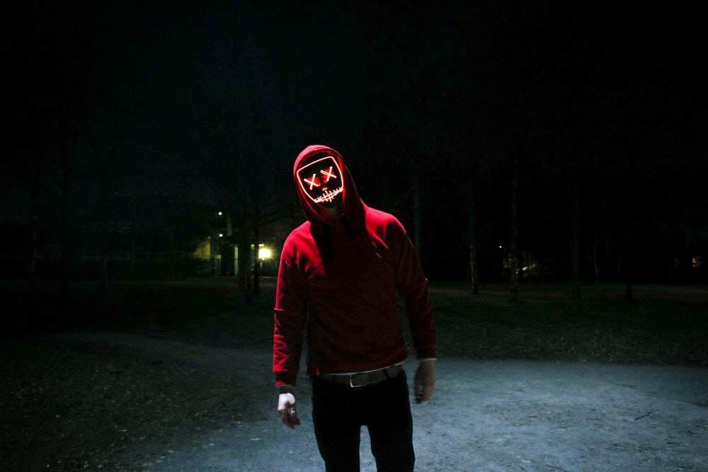 person in red pullover hooded jacket standing in street during nighttime