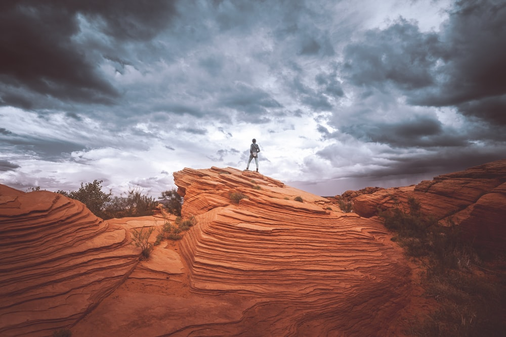 person standing on brown rock formation during daytime