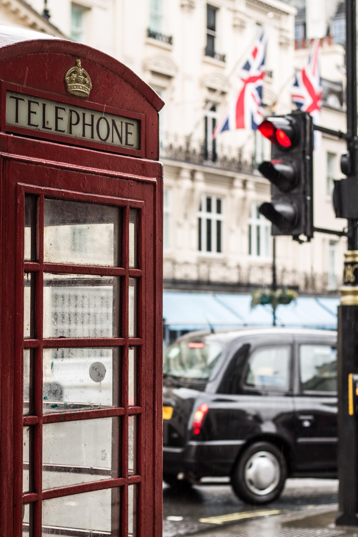telephone booth beside a black car