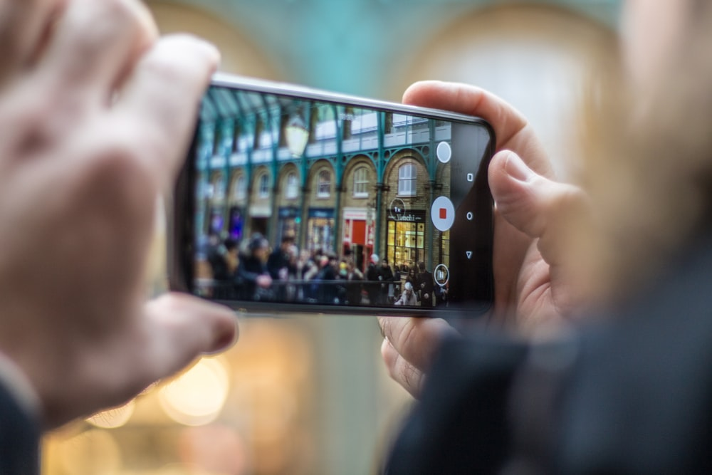 person holding smartphone taking video of people
