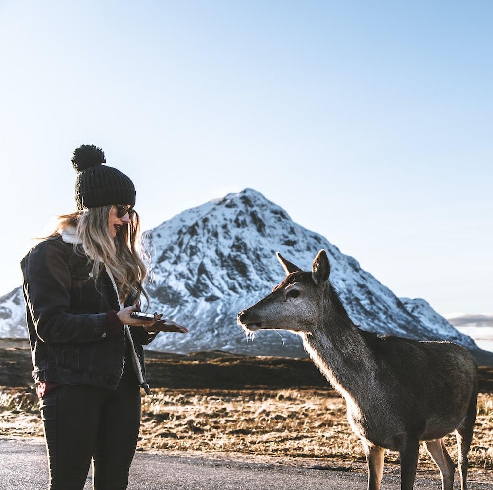 woman standing beside doe