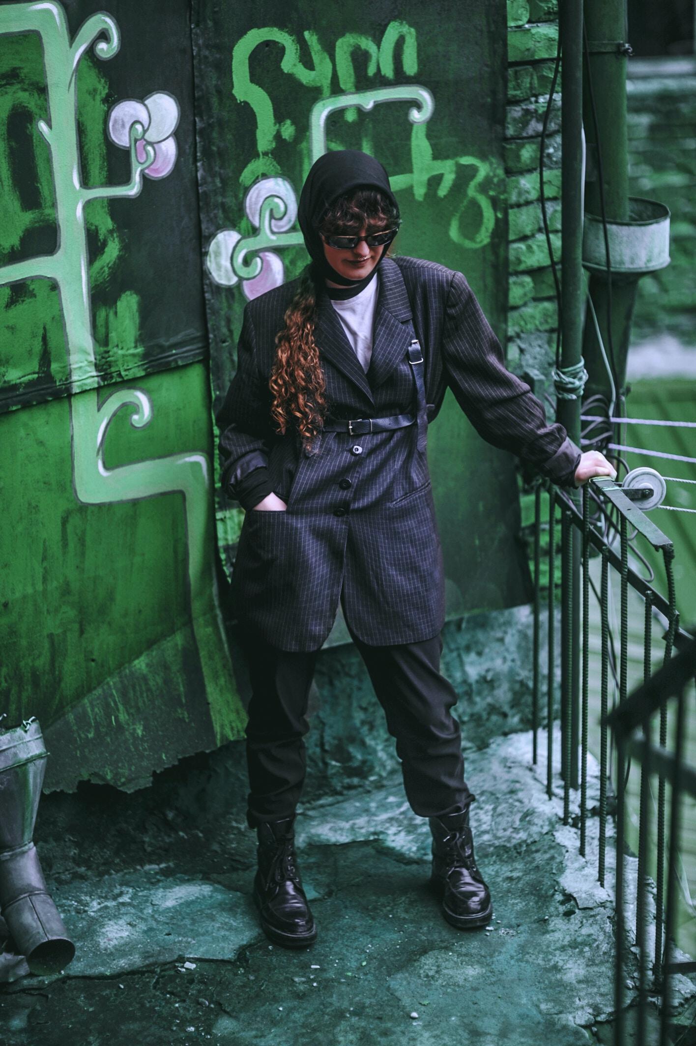 woman standing on corner holding metal rail